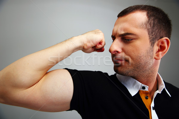 Man in casual cloth showing his biceps on gray background Stock photo © deandrobot