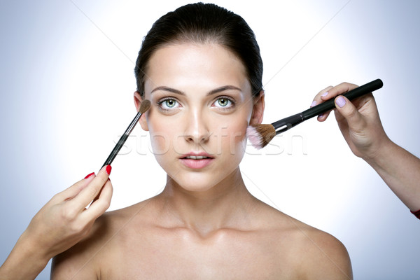 Closeup portrait of a woman applying dry cosmetic tonal foundation on the face using makeup brush Stock photo © deandrobot