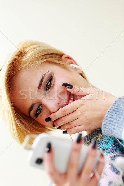 Young woman listening music and texting on her smartphone Stock photo © deandrobot