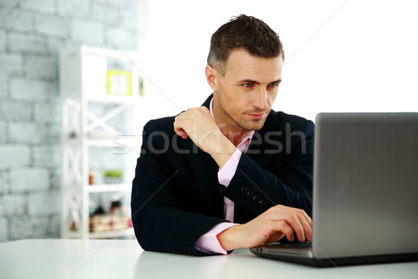 Confident businessman working on a laptop at office Stock photo © deandrobot