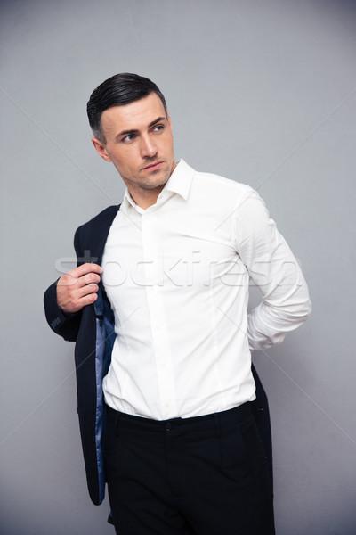 Businessman dressing jacket over gray background Stock photo © deandrobot