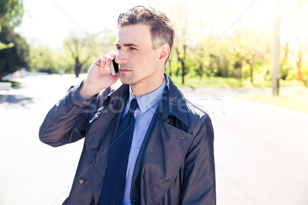 Confident businessman talking on the phone outdoors Stock photo © deandrobot
