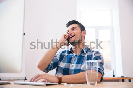 Young businessman speaking on the phone in office Stock photo © deandrobot