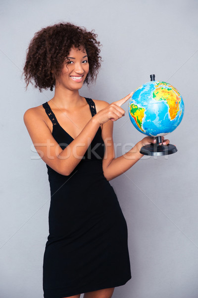 Happy african woman holding globe Stock photo © deandrobot
