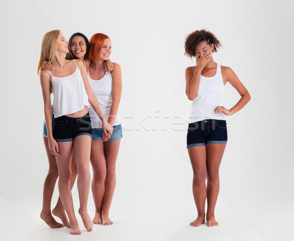 Afro american women standing while friends laughing with her  Stock photo © deandrobot