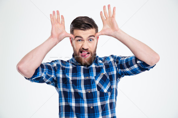 Man showing big ears with his hands and tongue Stock photo © deandrobot