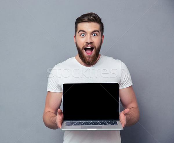 Alegre hombre ordenador portátil Screen gris Foto stock © deandrobot