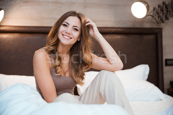 Cute curly girl sitting on bed Stock photo © deandrobot