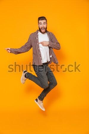 Podniecony szczęśliwy młody człowiek skoki uruchomiony Zdjęcia stock © deandrobot
