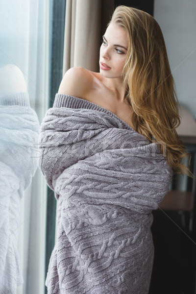 Attractive alluring female in grey coverlet looking through the window  Stock photo © deandrobot