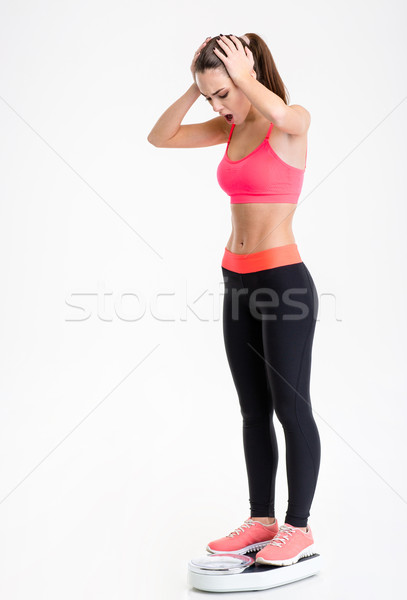 Beautiful shocked young sportswoman standing on weighing scale Stock photo © deandrobot