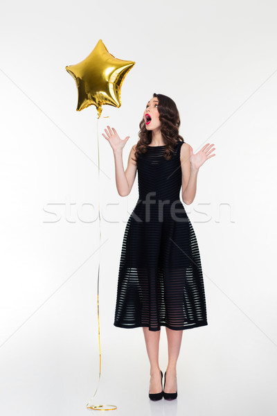 Amazed retro styled woman taking hands off from the balloon  Stock photo © deandrobot