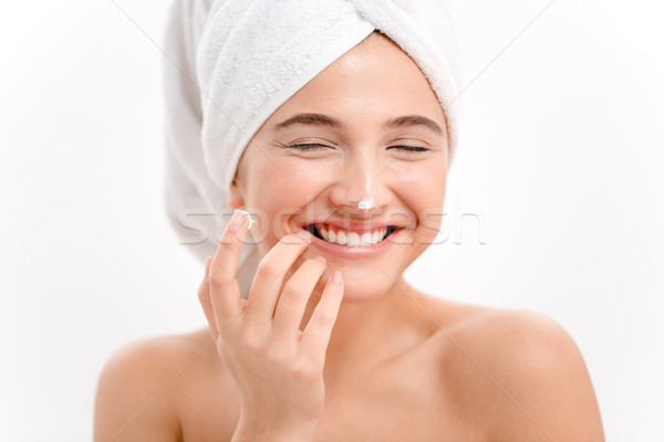 Cheerful attractive young woman with face cream on her nose Stock photo © deandrobot