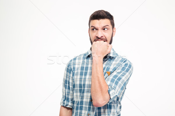 Angry irritated aggressive young bearded man biting his fist Stock photo © deandrobot