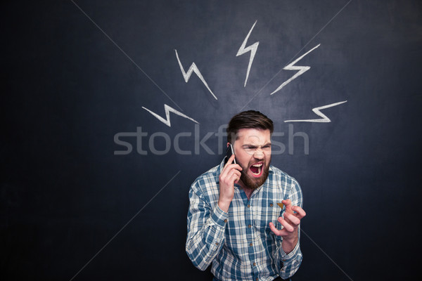 Mad man using cell phone and screaming over blackboard background Stock photo © deandrobot