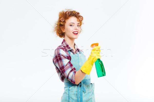 Sorridente dona de casa luvas de borracha limpeza garrafa Foto stock © deandrobot