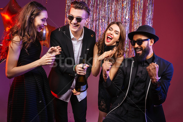Stock photo: Cheerful friends opening champagne and having fun together