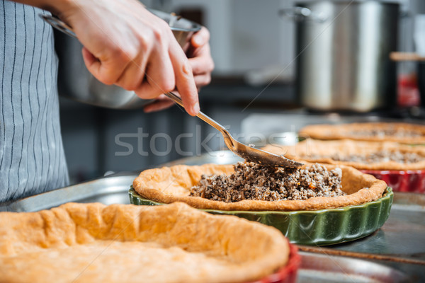 Hands of cheif cook cooking and putting filling into pie Stock photo © deandrobot