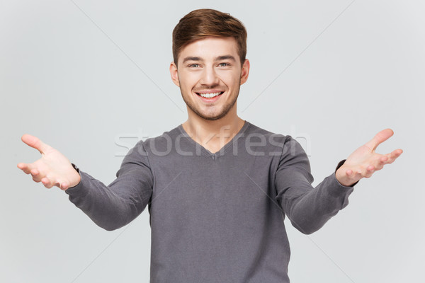 Cheerful handsome young man smiling and showing welcoming gesture  Stock photo © deandrobot