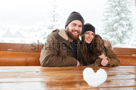 Couple sitting together at the wooden table on chalet patio Stock photo © deandrobot