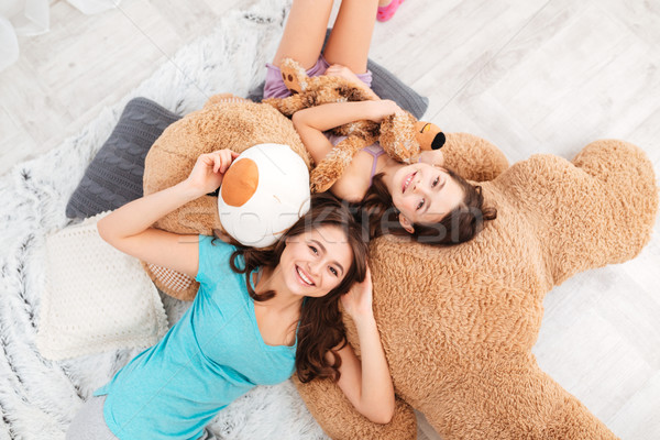 Two happy sisters lying on huge plush bear and laughing Stock photo © deandrobot