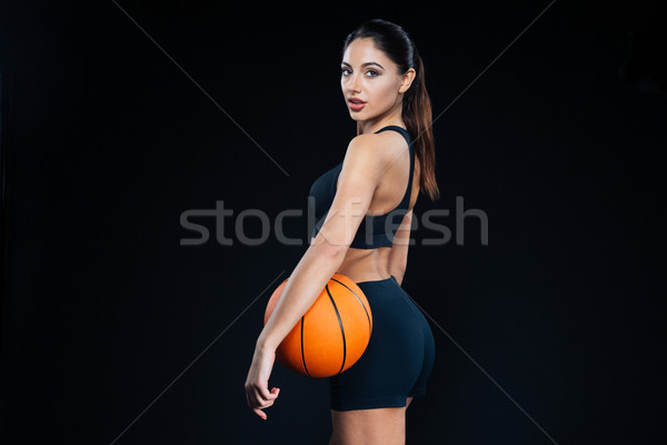 Stock photo: Fitness woman holding basketball ball and looking back at camera