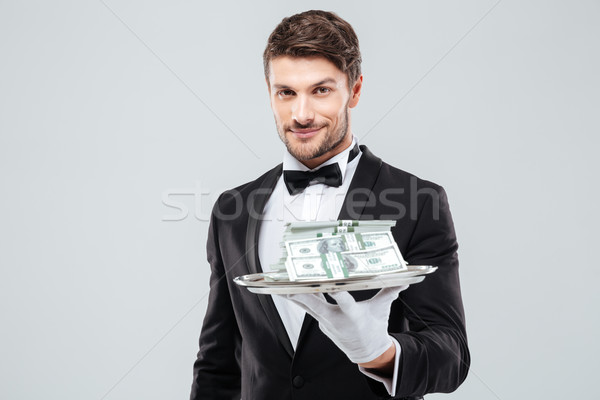 Smiling waiter in tuxedo and gloves holding tray with money Stock photo © deandrobot