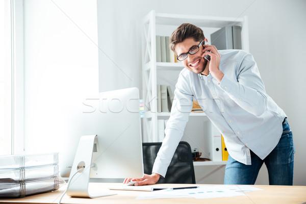 ストックフォト: 笑みを浮かべて · 小さな · ビジネスマン · 話し · 携帯電話
