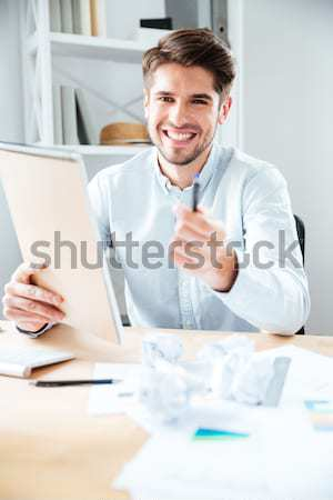 Stock photo: Happy young businessman reading notes in notpad