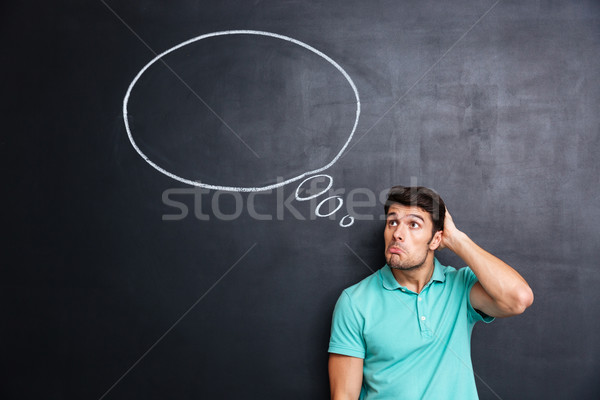 Thoughtful confused young man standing and thinking over blackboard background Stock photo © deandrobot