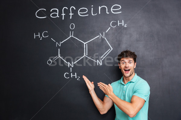 Happy excited young scientist showing chemical structure of caffeine molecule Stock photo © deandrobot