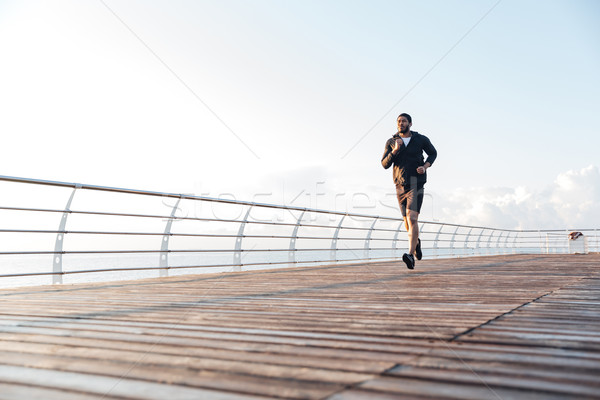 Sportsman listening to music and running in the morning Stock photo © deandrobot