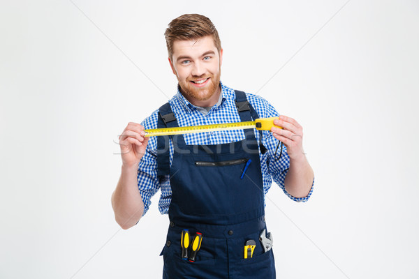Cheerful young worker in overall smiling and holding measuring tape Stock photo © deandrobot