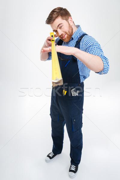 Jóképű fókuszált fiatalember munkás áll mérőszalag Stock fotó © deandrobot