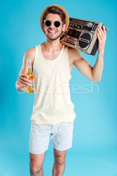 Smiling handsome young man with boombox and bottle of beer Stock photo © deandrobot