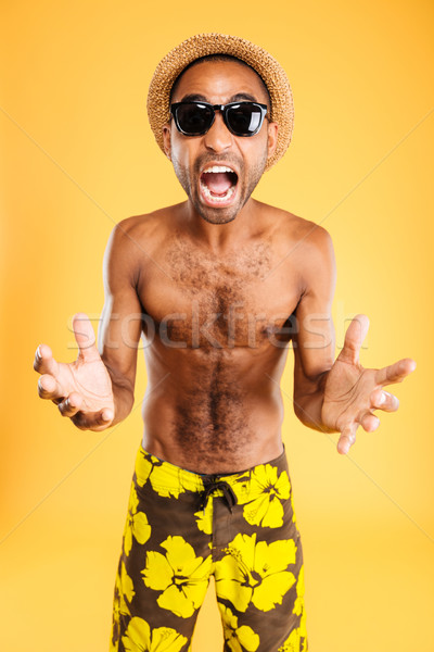 Angry mad african man in swimwear standing and shouting Stock photo © deandrobot