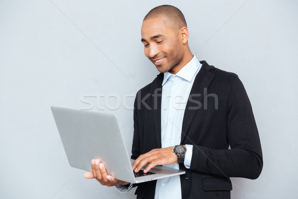 Smiling african american young man standing and using laptop Stock photo © deandrobot