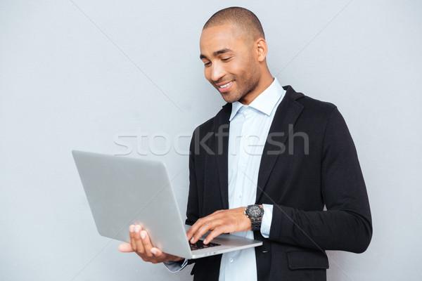Mosolyog afroamerikai fiatalember áll laptopot használ internet Stock fotó © deandrobot