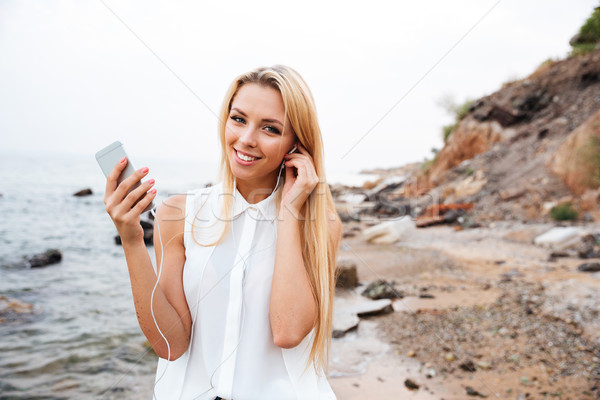 Woman listening music with smartphone while standing at the beach Stock photo © deandrobot