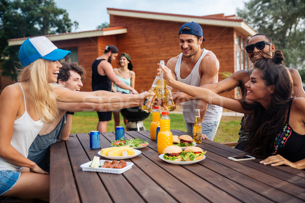 Group of young cheerful friends having fun at picnic outdoors Stock photo © deandrobot