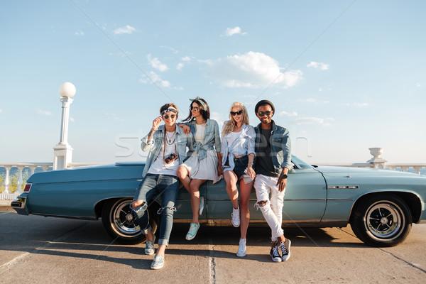 Happy friends standing near vintage car Stock photo © deandrobot