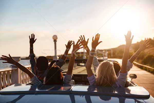 Back view of happy friends driving cabriolet with raised hands Stock photo © deandrobot