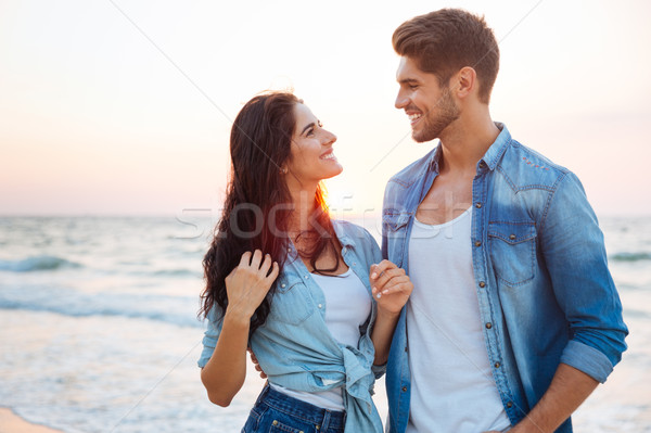 Couple standing and looking at each other on the beach Stock photo © deandrobot