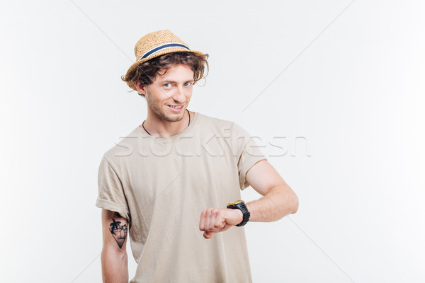 Portrait of a smiling man looking on wrist watch Stock photo © deandrobot