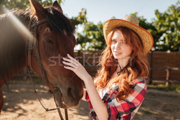 Attractive redhead young woman cowgirl in hat with her horse Stock photo © deandrobot
