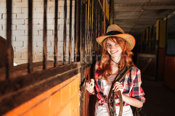 Happy beautiful young woman cowgirl standing in stable Stock photo © deandrobot
