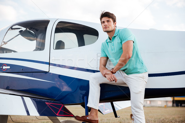 Young man pilot standing near small aircraft Stock photo © deandrobot