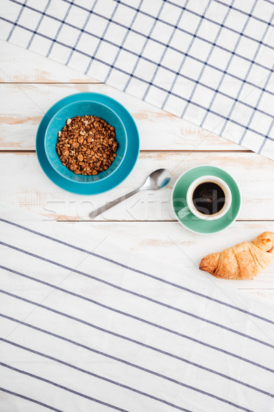 Cereals, cup of coffee, croissant with striped and plaid napkins Stock photo © deandrobot