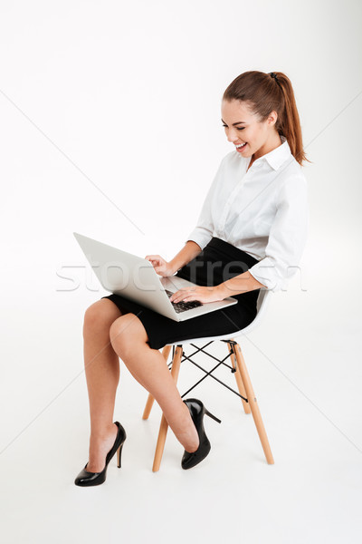 Portrait femme d'affaires utilisant un ordinateur portable chaise de bureau souriant isolé Photo stock © deandrobot