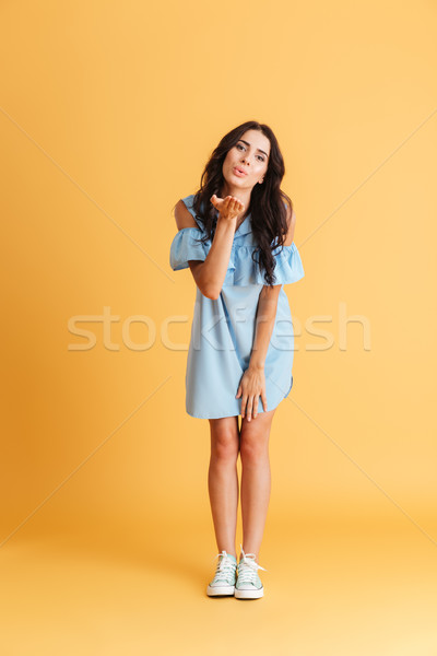 Young woman in blue dress sending air kiss to camera Stock photo © deandrobot